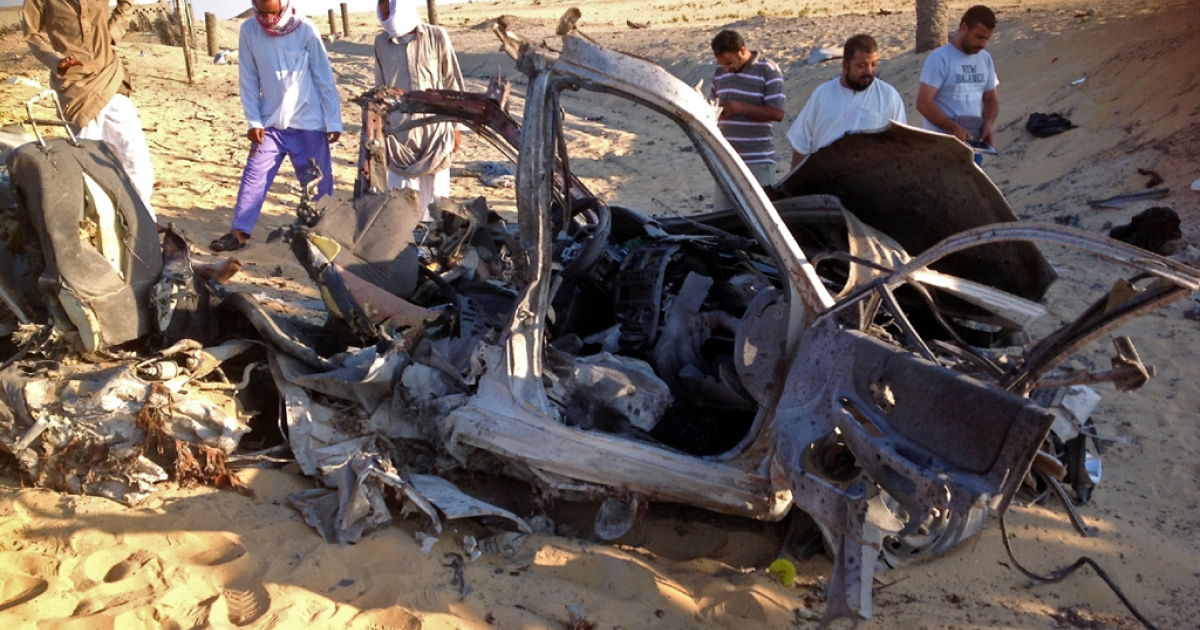 Egyptians gather near a damaged car bomb that detonated before reaching the intended target killing three passengers on July 24, 2013,in El-Arish in Egypt's Sinai peninsula. The bomb went off as the assailants entered the north Sinai town of El-Arish, where two soldiers were killed in separate shooting attacks earlier, said security officials.</p>