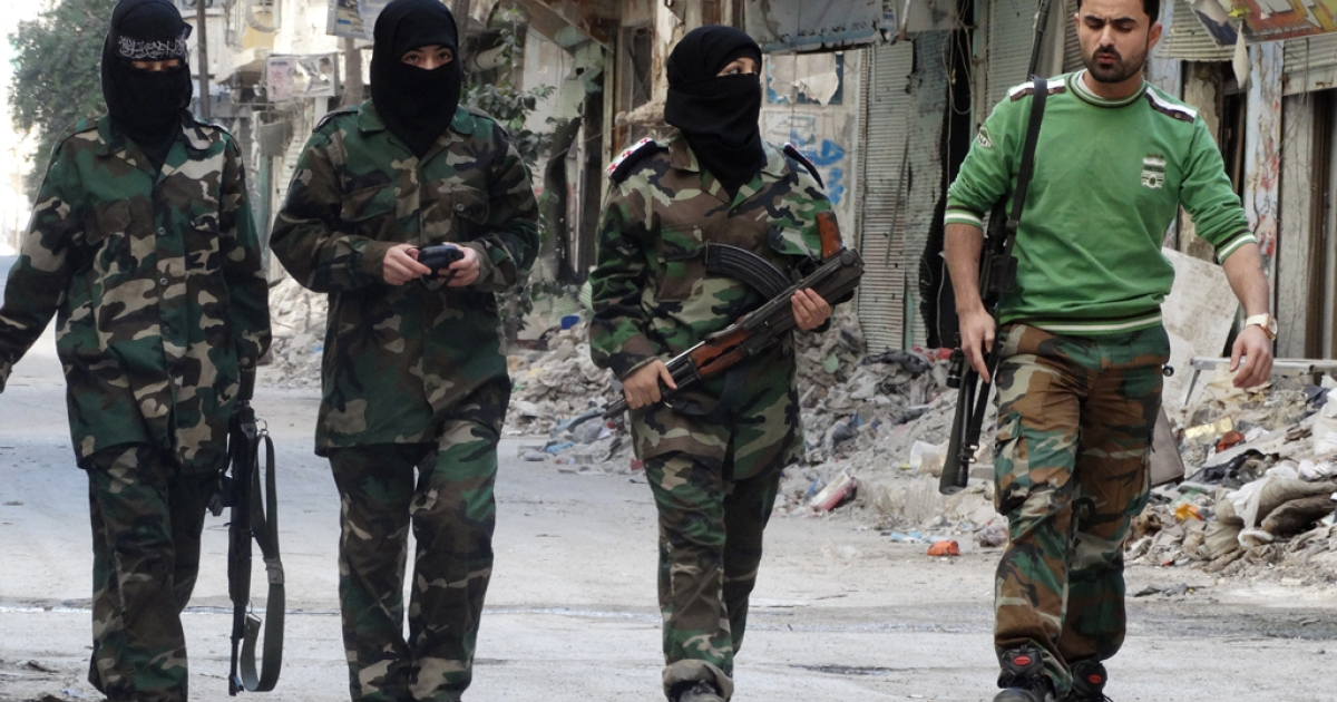 Masked female rebel fighters walk alongside their trainer in a street at the Salaheddin district of the war-battered northern Syrian city of Aleppo on October 8, 2013.</p>