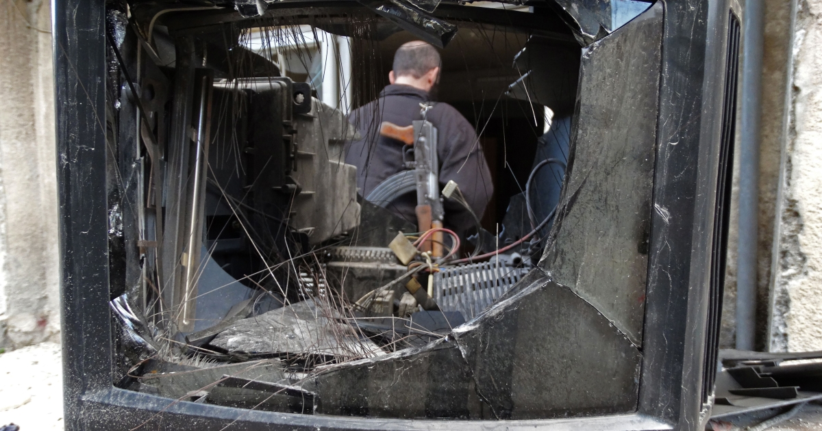 A picture taken on Oct. 18, 2013, shows a rebel fighter standing behind a broken television in the Salaheddin district of the northern Syrian city of Aleppo. The Syrian Observatory for Human Rights reported dozens of deaths in the northern province of Aleppo as UN-Arab League representative Lakhdar Brahimi prepares a Middle East tour ahead of proposed peace talks next month.</p>