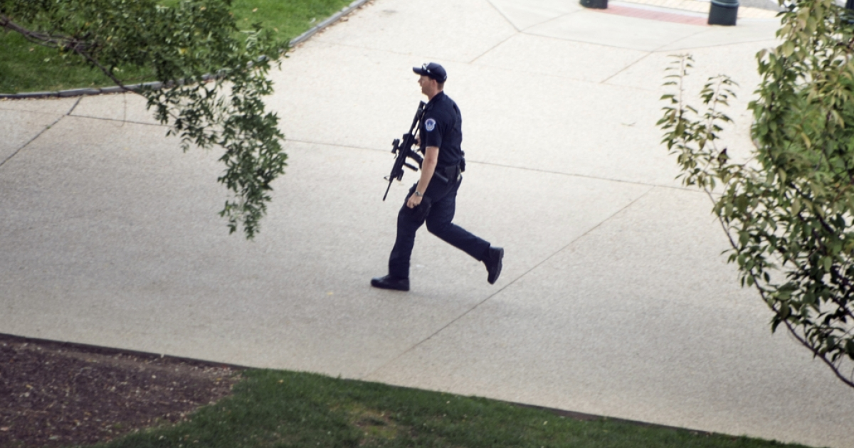A US Capitol Police officer runs while reacting to a call of shots fired on Capitol Hill October 3, 2013 in Washington, DC. The US Capitol was placed on security lockdown Thursday after shots were fired outside the complex, senators said.</p>