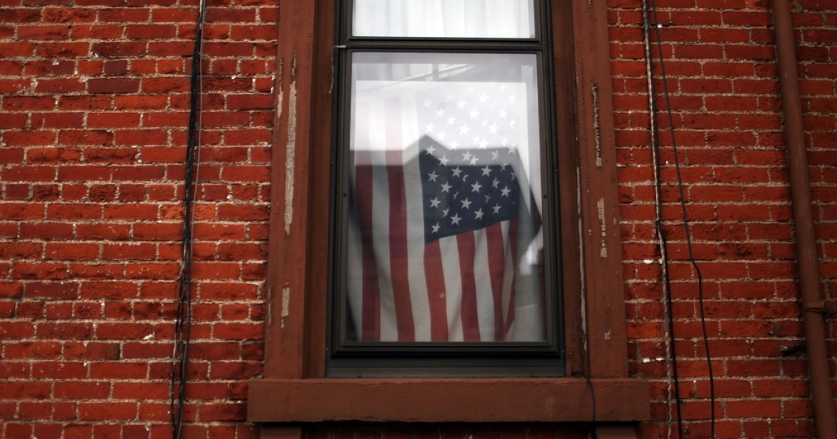 A flag hangs in a window in Utica, NY.</p>