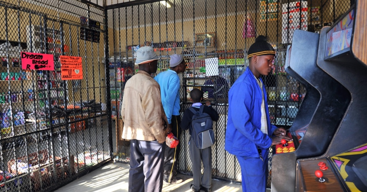 People queue to buy goods in a shop in Soweto, where the owner, a Bangladeshi immigrant, has fortified the cash desk behind iron bars. More than 100 shops owned by Somali immigrants in Port Elizabeth have been looted in a four-day outbreak of xenophobic attacks, police said on Sept. 18, 2013.</p>