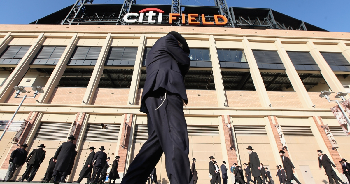 Ultra-Orthodox Jews gather before entering Citi Field for a meeting to discuss the risks of using the Internet on May 20, 2012 in the Queens borough of New York City. More than 40,000 were expected to attend the rally at Citi Field, the home of the New York Mets, which organizers said would promote religiously responsible ways to use the Internet.</p>