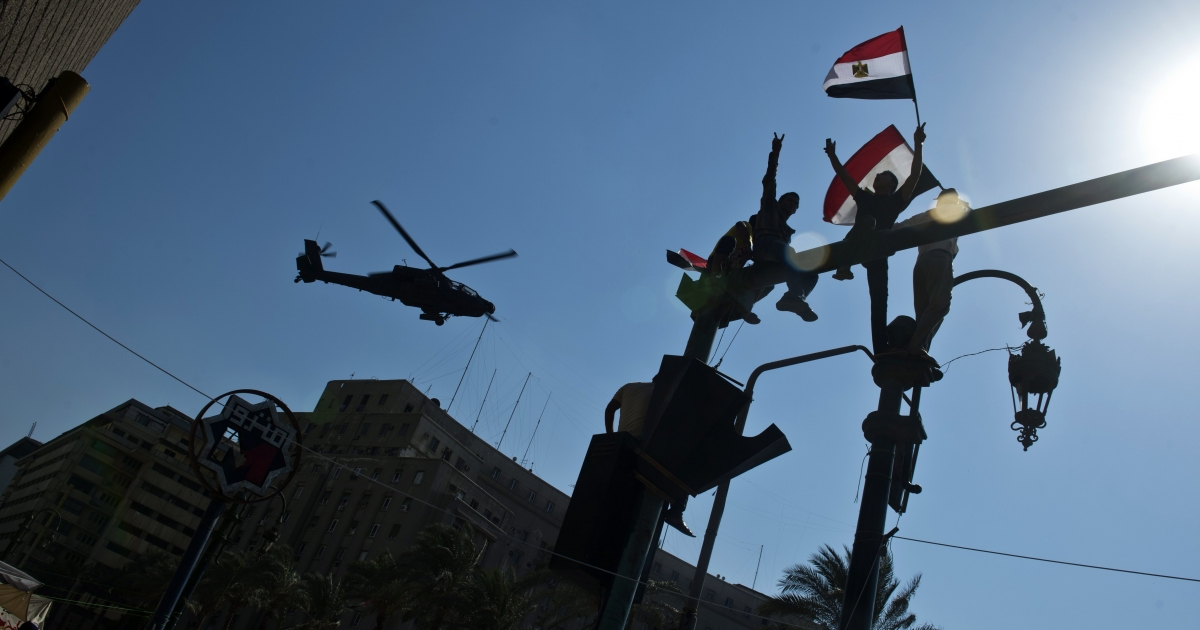 Supporters of army chief General Abdel Fattah al-Sisi wave the Egyptian flag as an army helicopter flies over Tahrir Square in Cairo on July 16, 2013. Egypt's authorities formally detained Mohamed Morsi on suspicion of collaborating with Palestinian militants in murdering policemen and staging prison breaks, as tens of thousands of the deposed president's supporters and opponents staged rival rallies.</p>