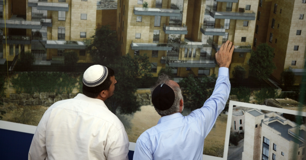 Israelis stand next to sales promotion sign after a corner stone laying ceremony for a new Jewish neighborhood on August 11, 2013 in East Jerusalem, Israel. Israel's Housing Ministry announced Sunday the marketing of land for the immediate construction of nearly 1,200 new units in Jewish neighborhoods in East Jerusalem and the West Bank settlement blocs.</p>