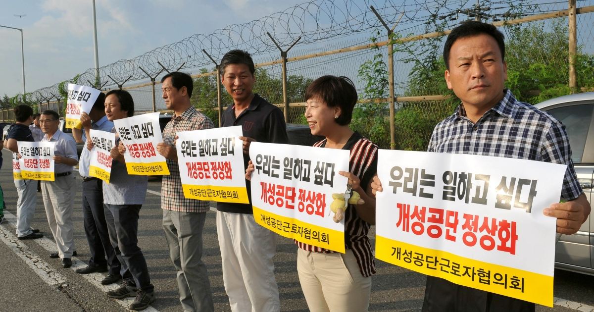 South Korean representatives from Kaesong-based companies hold placards reading