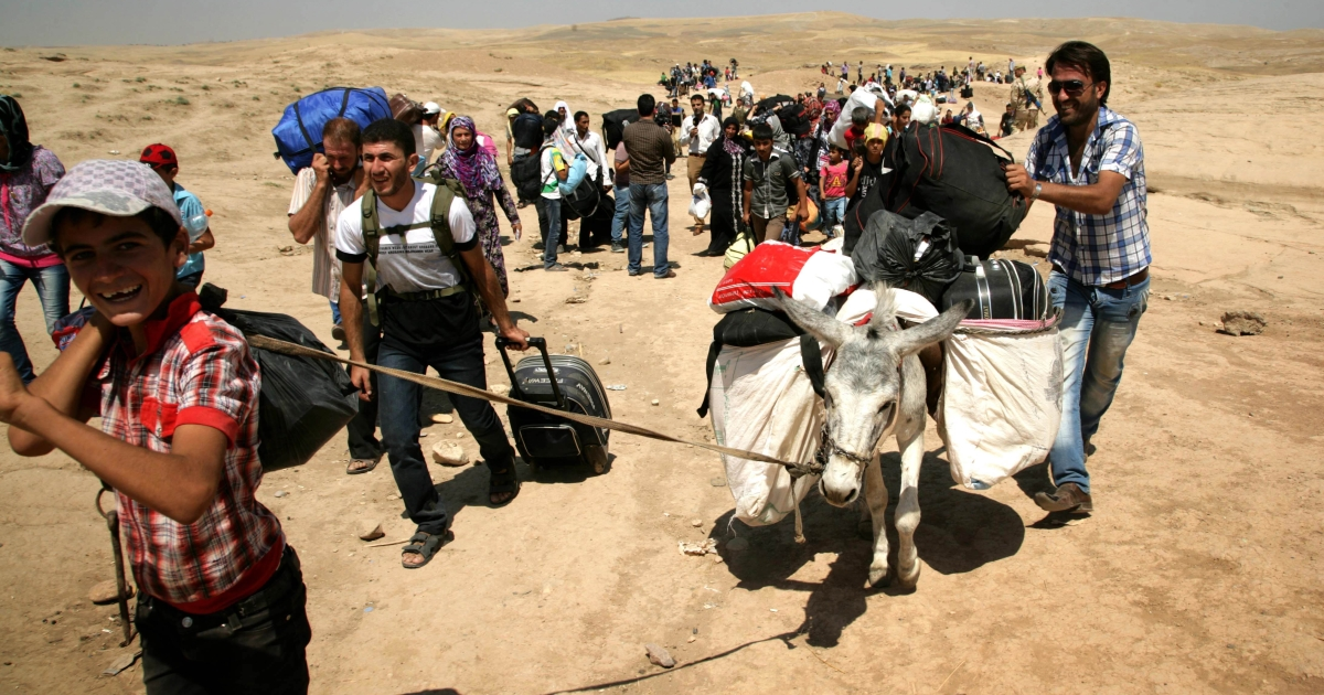 Syrian refugees cross the border into the autonomous Kurdish region of northern Iraq, on August 18, 2013. Faced with brutal violence and soaring prices, thousands of Syrian Kurds have poured into Iraq's autonomous Kurdish region, seeking respite from privation and fighting between Kurdish fighters and jihadists.</p>