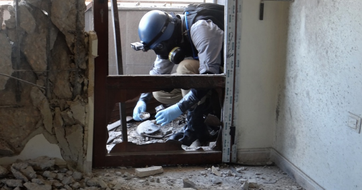 A United Nations arms expert collects samples from the site of an attack in the eastern suburbs of Damascus, on August 29, 2013. Human Rights Watch has concluded from its own investigation that Syrian government forces fired chemical weapons in the August 21 attack, which killed hundreds of people.</p>