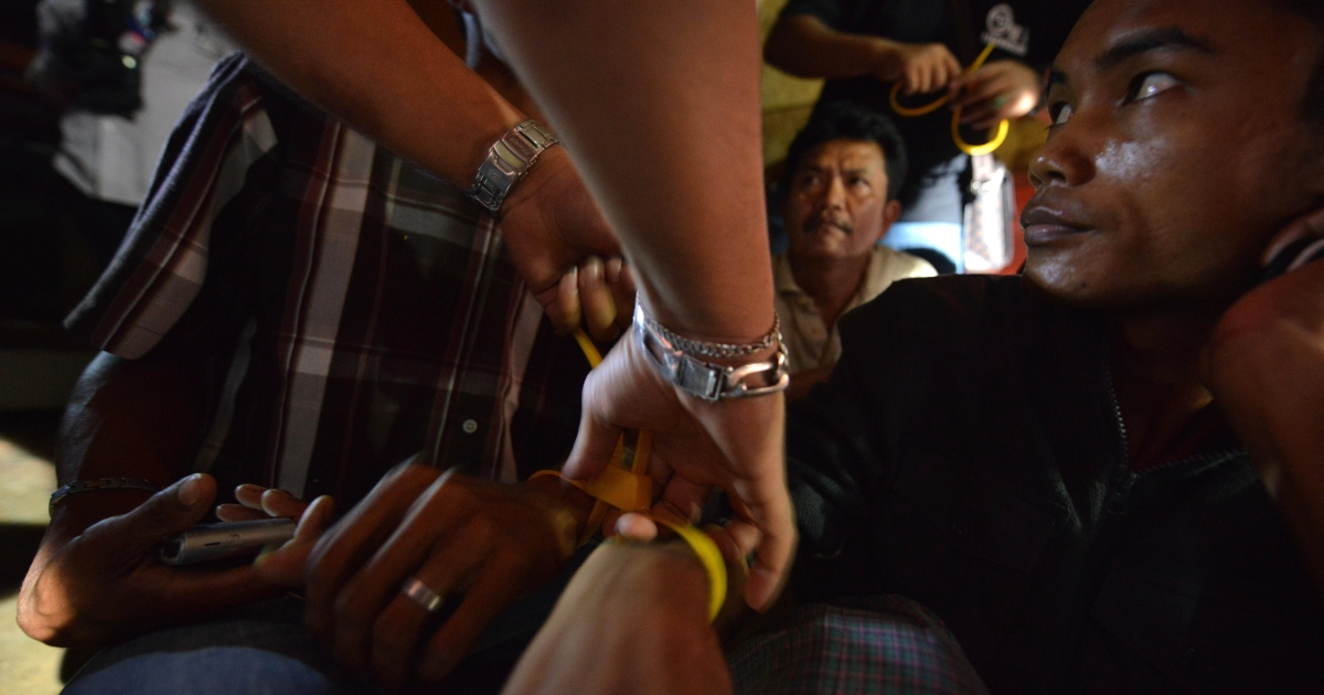 A Malaysian Immigration officer putting zip-ties on the wrists of suspected illegal foreign workers during an immigration raid operation shortly after midnight in Klang, outside Kuala Lumpur on September 1, 2013.  Malaysia began casting a nationwide dragnet early on September 1 over an estimated half a million illegal foreign workers amid a crime wave that has cast the nation's focus on security. Enforcement officers from the immigration headquarters in the administrative capital Putrajaya nabbed 73 in the wee hours of the morning, an official said while awaiting reports from branches across the country.</p>