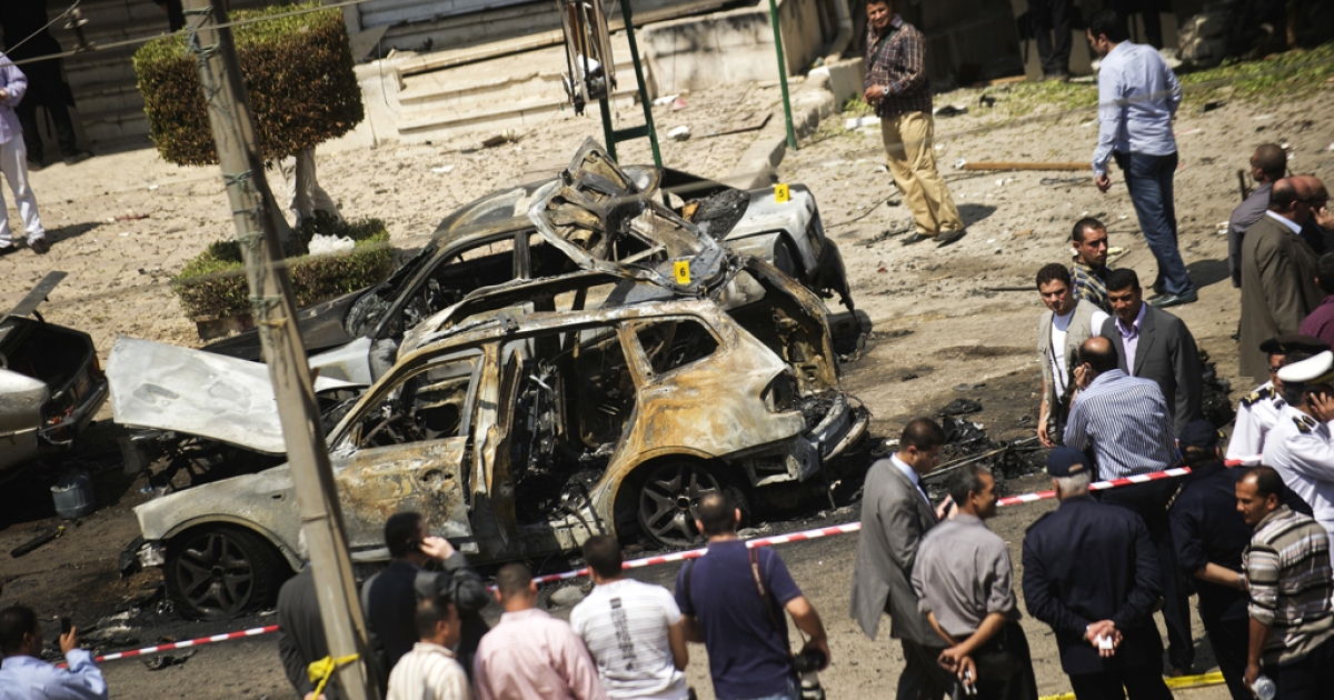 Egyptians gather at the site of a bomb that targeted the convoy of the Egyptian Interior Minister Mohammed Ibrahim in Cairo on September 5, 2013. It was the first such attack in Cairo in years.</p>