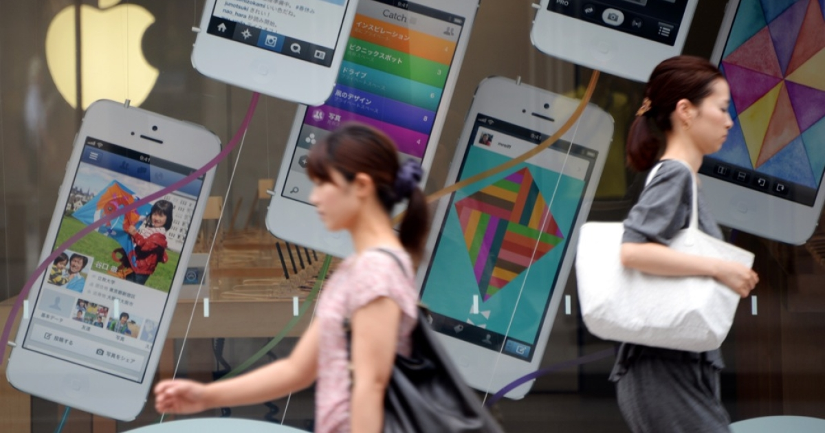 Pedestrians walk past advertisements for the iPhone 5 at the Apple store in central Tokyo on September 6, 2013.</p>