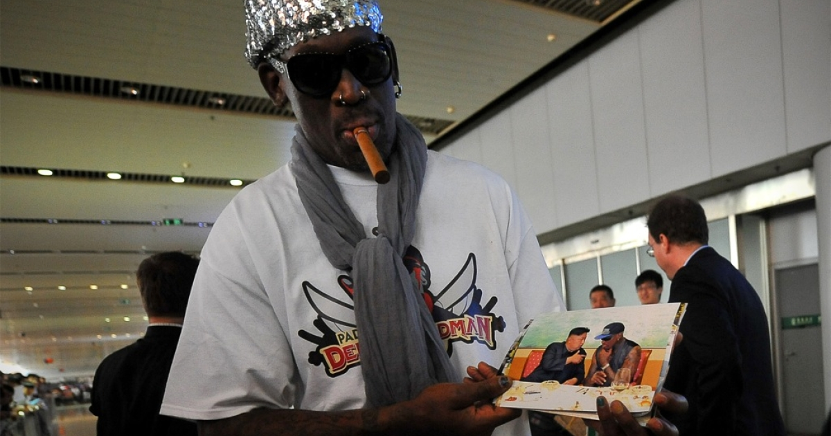 Family album: former NBA star Dennis Rodman shows pictures of himself with Kim Jong Un on the way home from a trip to North Korea, at Beijing airport on Sept. 7, 2013. Rodman says the supreme leader, who reportedly has a baby daughter, is a