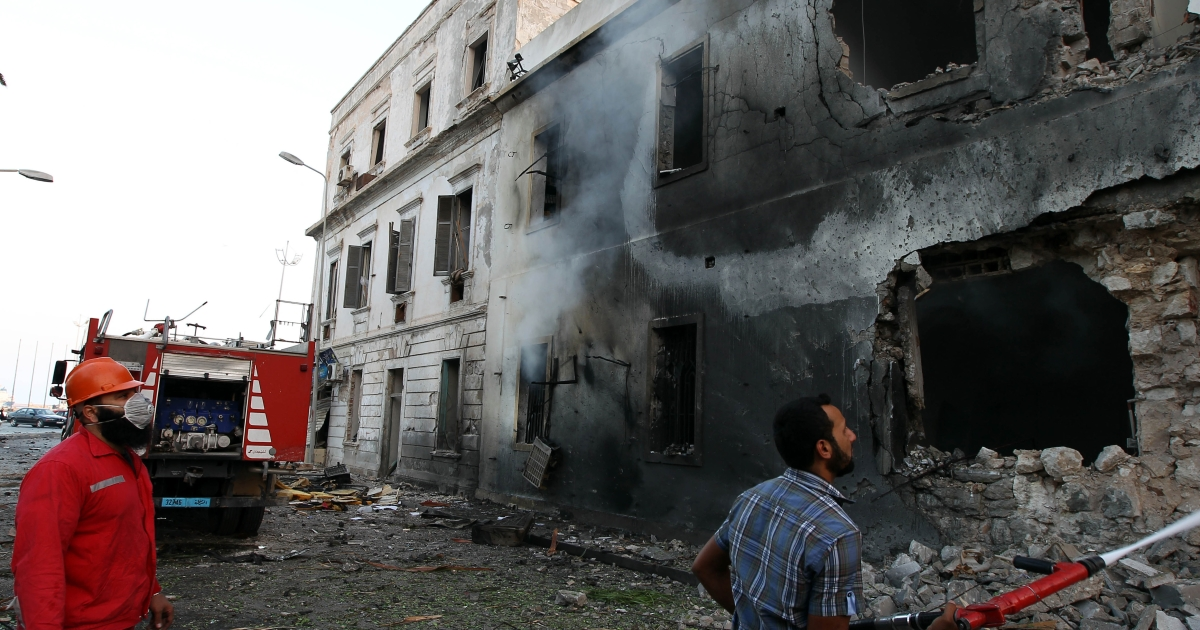 Libyan firefighters extinguish a fire caused by a powerful blast near a foreign ministry building on September 11, 2013 in the eastern Libyan city of Benghazi. The explosion comes on the first anniversary of an attack by militants on the United States consulate in Benghazi, which killed four Americans, including the ambassador.</p>