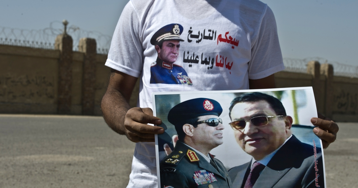 A supporter holds a poster featuring Egyptian toppled president Hosni Mubarak (R) and General Abdel Fattah al-Sisi (L) on September 14, 2013 in Cairo outside the Police Academy, where Mubarak appeared in court for the second time since his release from Cairo's Tora prison. Mubarak faces an array of charges, including complicity in the deaths of some 850 people killed in the Arab Spring-inspired uprising against him, and corruption.</p>