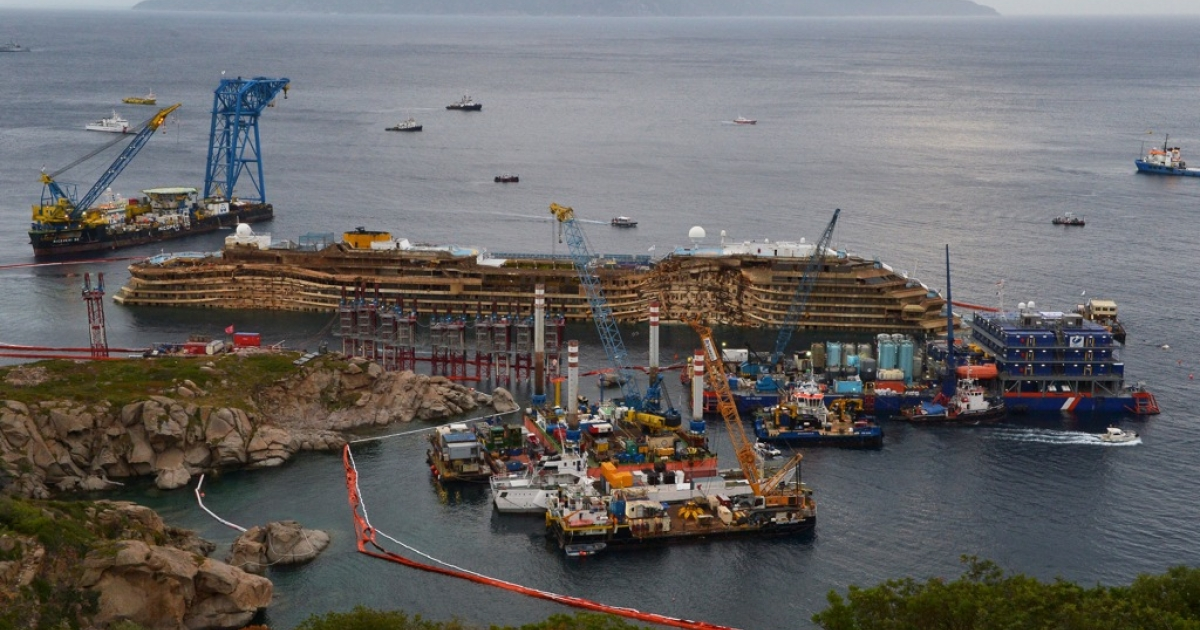 A picture taken on September 17, 2013 shows the wreck of the Costa Concordia as it begins to emerge from water near the Italian island of Giglio. Salvage operators lifted the cruise ship upright from its watery grave in the biggest ever project of its kind.</p>