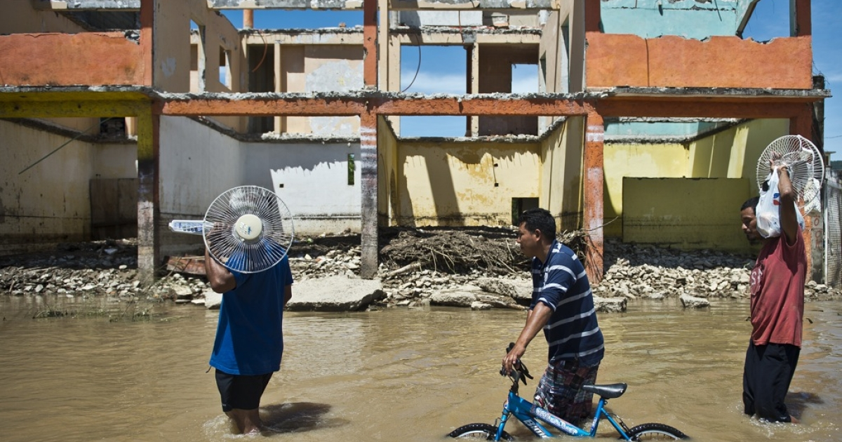 Local residents wade through a flooded street in Acapulco, state of Guerrero, Mexico, on September 18, 2013 as heavy rains hit the country. Two tropical storms, Ingrid and Manuel, hit large swaths of the country during a three-day holiday weekend, triggering landslides and causing rivers to overflow in several states.</p>