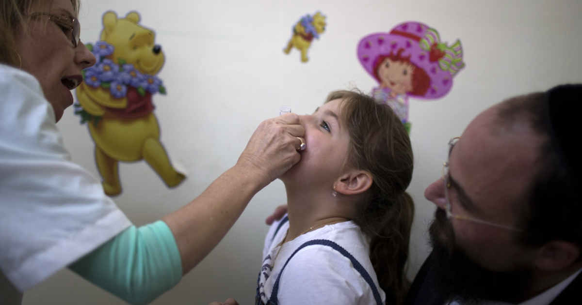 An Israeli child receives a vaccination against Polio at a clinic in Jerusalem on August 18, 2013. Israel took its polio vaccination campaign nationwide.</p>