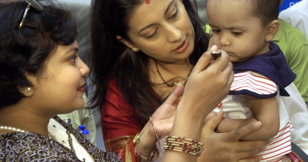 World Health Organisation (WHO) and Oral Rehydration Salts (ORS) Goodwill Ambassador Smriti Irani (C) holds a child being fed an ORS solution.</p>