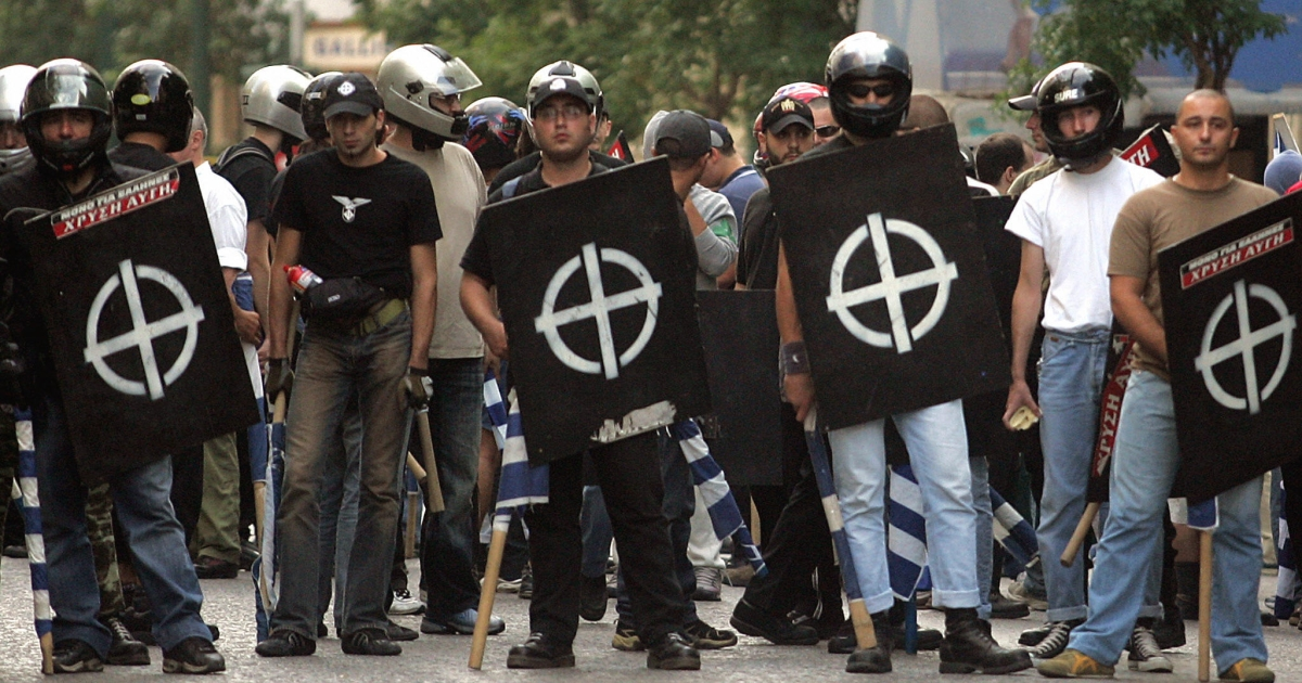 Extreme right-wing group Chryssi Avgi (Golden Dawn) members hold greek flags and their's faction's emblem 17 september 2005 during a demonstration outside their headquarters in central Athens to protest a ban on a planned gathering of European neo-Nazi and fascist parties in Greece.</p>