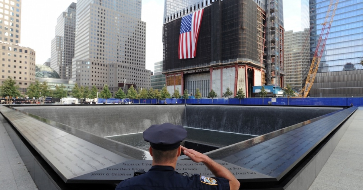 York City Police Officer Danny Shea salutes at the North pool of the 9/11 Memorial on Sept. 11, 2011 in New York City.</p>