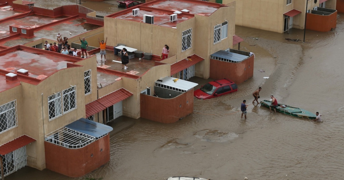 Residents wait for help in Acapulco, state of Guerrero, Mexico, on Sept. 17, 2013 as heavy rains hit the country.</p>