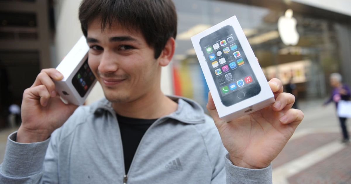 Kerim Muhammet poses with his two new Apple iPhone 5S models after waiting in line overnight in Glendale, California, on September 20, 2013. Apple launched two new models of the iPhone today, the iPhone 5S, which is an updated version of the iPhone 5, and a less expensive iPhone 5C.</p>
