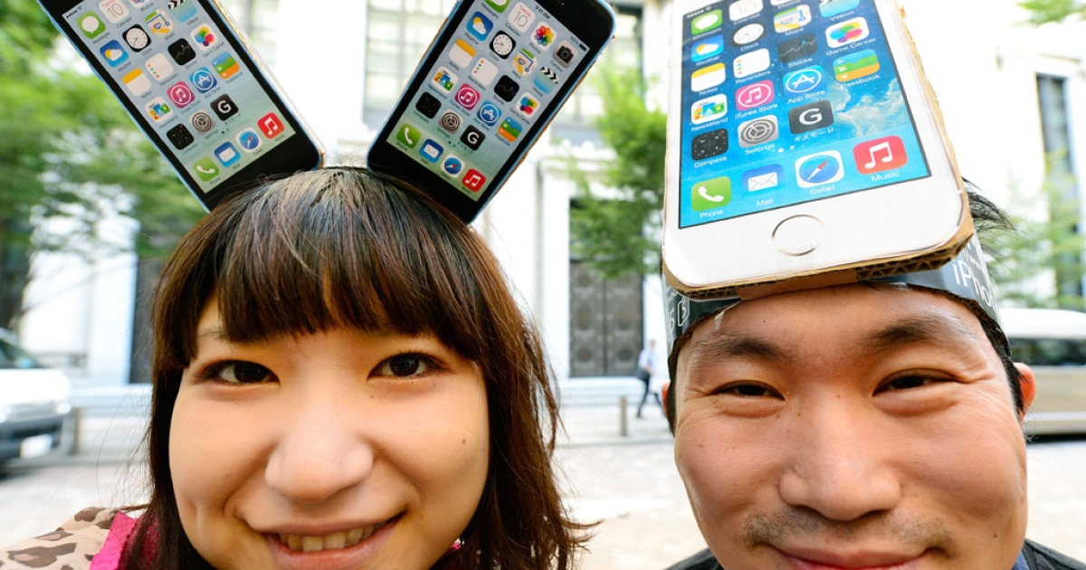 Apple fans wearing handmade iPhone headpieces smile as they wait to purchase the new iPhone 5s outside an outlet of Japan's biggest mobile carrier, NTT Docomo, in Tokyo on September 20, 2013.</p>