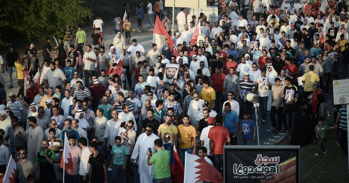 Bahraini protesters wave their national flags as they take part in an anti-government protest in the village of Jannusan, west of the capital Manama, on September 27, 2013. Thousands took to the streets in Bahrain to condemn the arrest of ex-MP Marzooq, hours after clashes between protesters and police, officials and witnesses said. AFP PHOTO/MOHAMMED AL-SHAIKH</p>