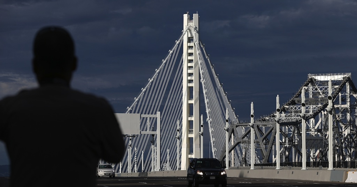 A California Highway Patrol officer looks on as a procession of cars crosses the new eastern span of the San Francisco Oakland Bay Bridge following a chain-cutting ceremony to mark the opening of the bridge on September 2, 2013 in San Francisco, California. After nearly 12 years of construction and an estimated price tag of $6.4 billion, the new eastern span of the Bay Bridge will open to traffic a day ahead of schedule. The bridge will be the world's tallest Self-Anchored Suspension (SAS) tower once completed.</p>