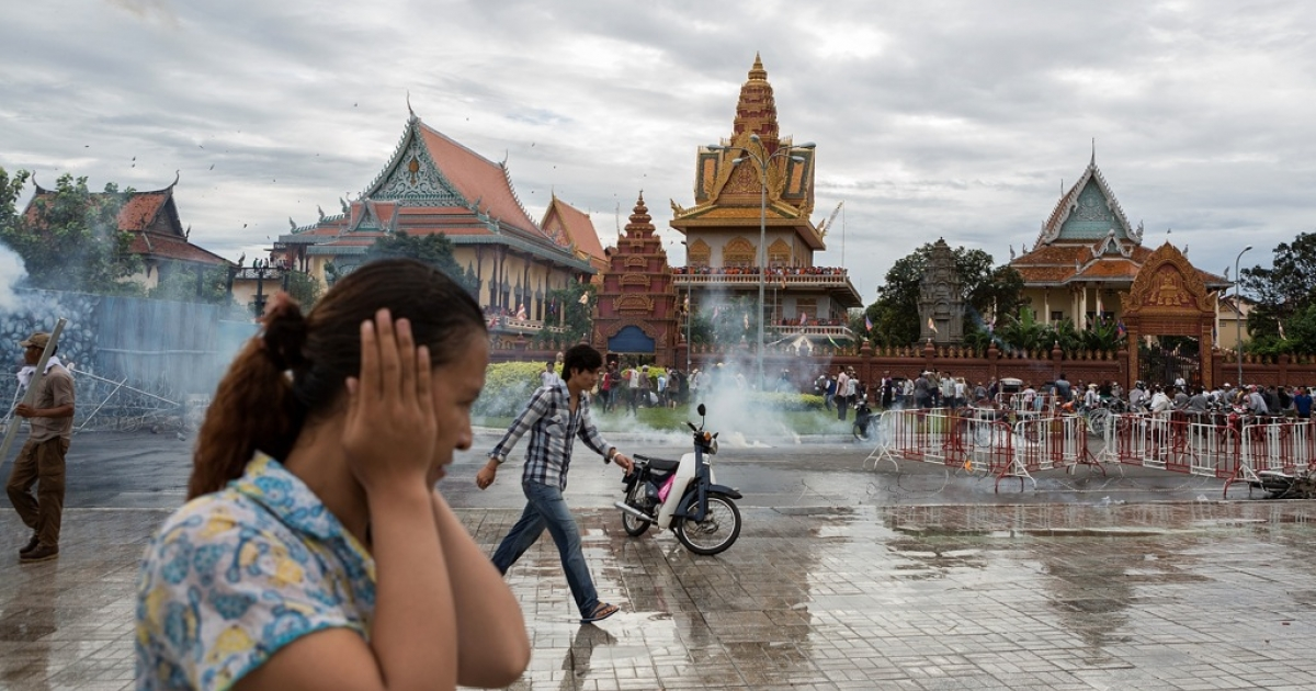 Anti-riot police fire tear gas as clashes erupt near the riverside on Sept. 15, 2013, in Phnom Penh, Cambodia.</p>
