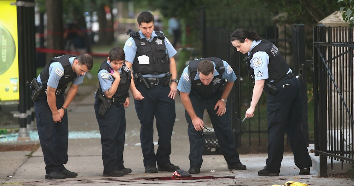 Chicago police investigate a shooting in front of the Uptown Baptist Church on Aug. 19, 2013 in Chicago, Illinois.</p>