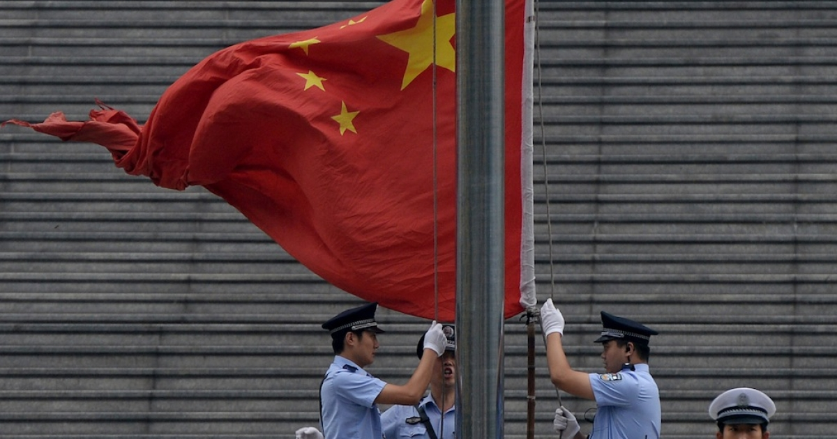 Police raise the Chinese flag outside the Intermediate People's Court in Jinan, Shandong Province on Sept. 22, 2013.</p>