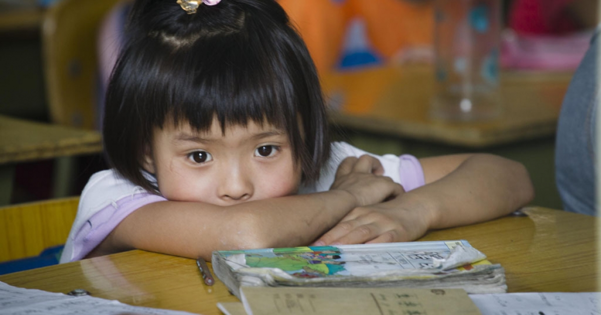 A young girl studies at an illegal migrant school ordered to close in Beijing, China. In a country facing geographical and economic challenges to its education system, an estimated 400 million people can't speak Mandarin, the national language, state media reported on Sept. 5, 2013.</p>