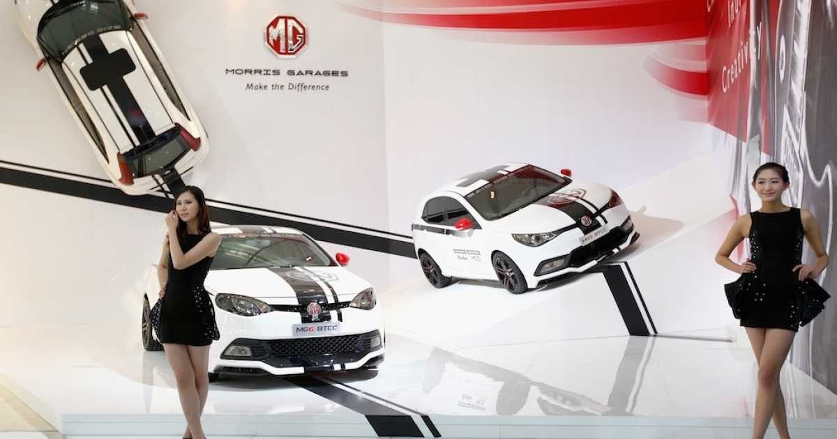 Models stands beside a MG6 Btcc car during the 2012 Beijing International Automotive Exhibition. China's capitalism may be cut-throat like America's, but it's played under an entirely different set of rules, says Andrew Hubert, publisher of ChinaSolved.com.</p>
