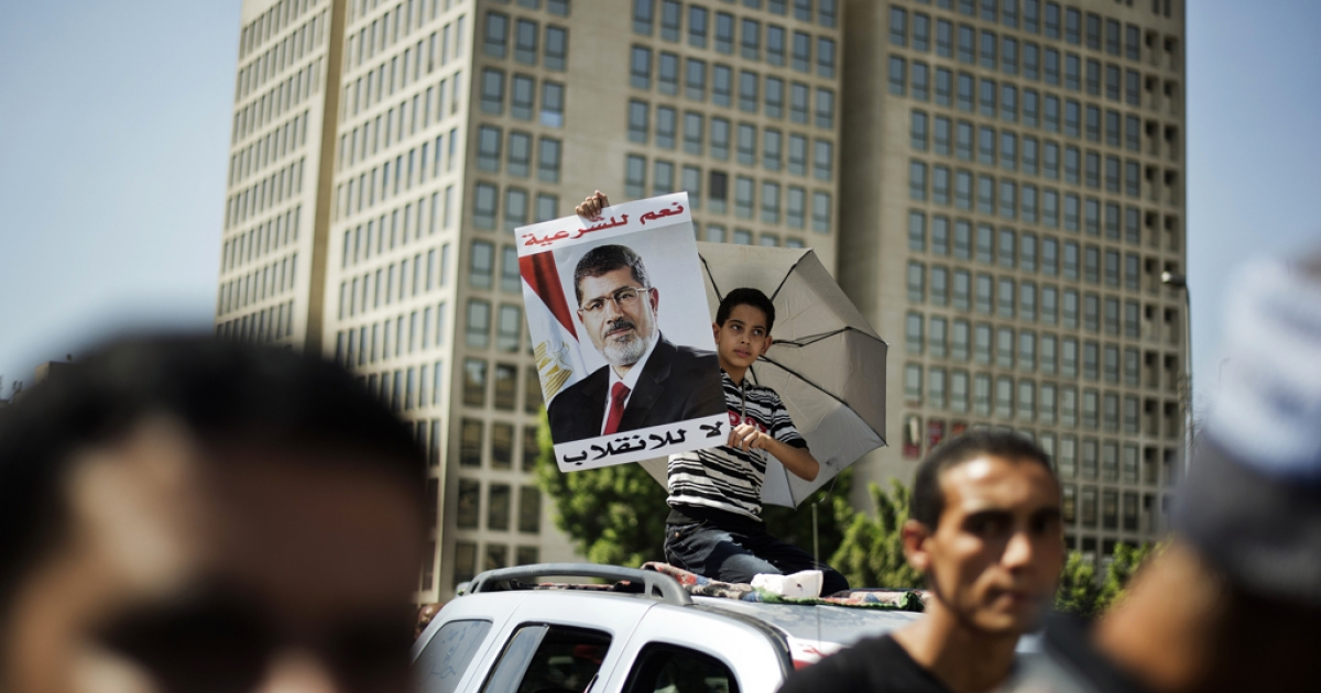 An Egyptian child carries a portrait of ousted president Mohamed Morsi during a demonstration in support of Morsi in Cairo, on August 9, 2013.</p>