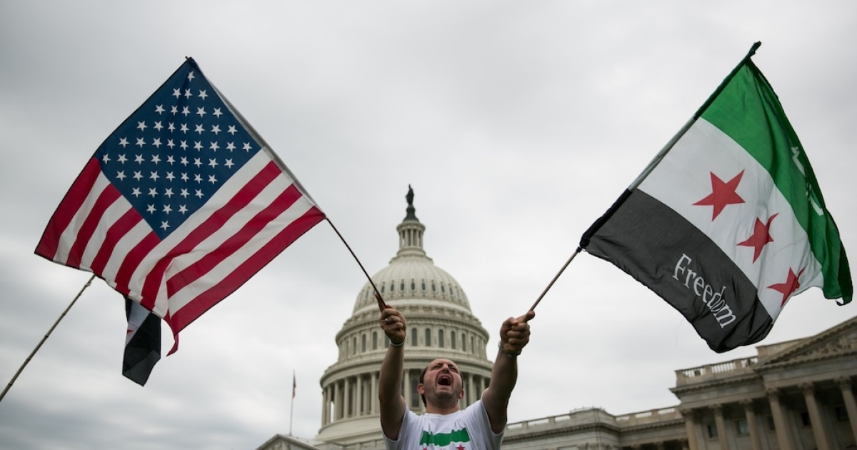 WASHINGTON, DC - SEPTEMBER 9: Jehad Sibai waves flags during a rally in support of possible U.S. military action in Syria, on Capitol Hill, on September 9, 2013 in Washington, DC. A Syrian minister has called the US-Russia chemical weapons deal struck in Geneva on Saturday a