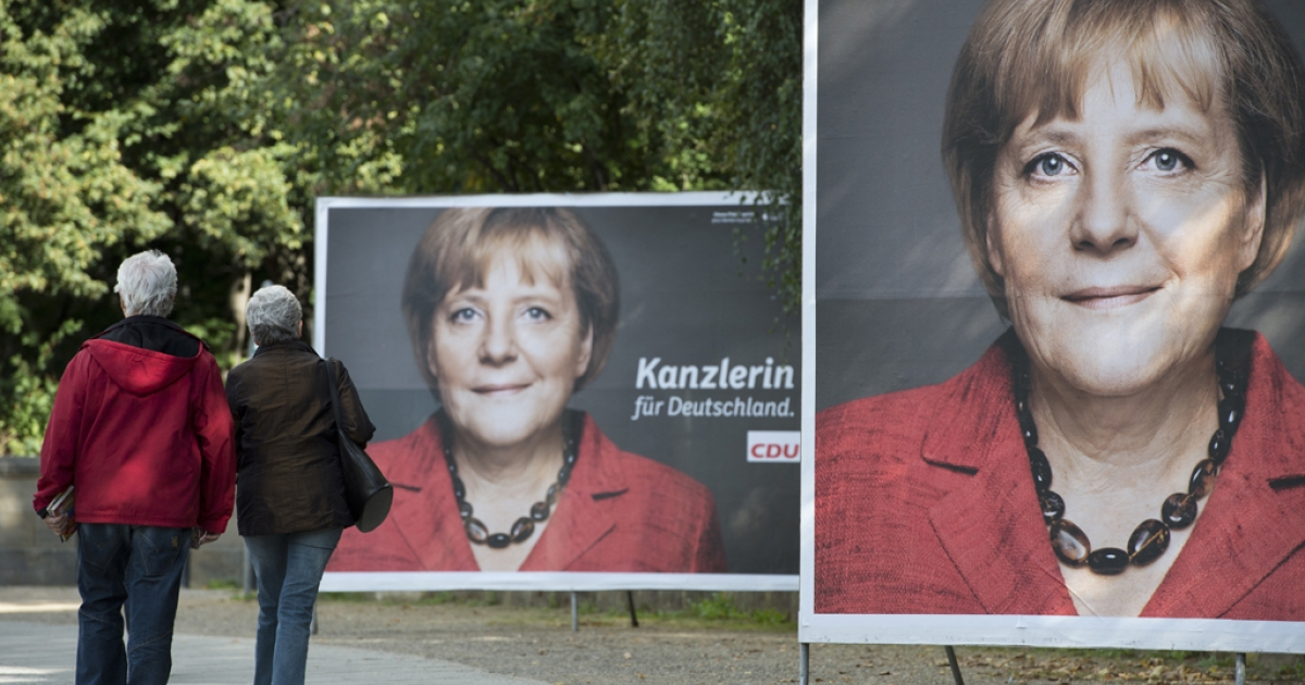 A couple makes their way past election posters featuring German Chancellor Angela Merkel in Berlin September 17, 2013.  Germany goes to the polls in general elections on September 22, 2013.</p>