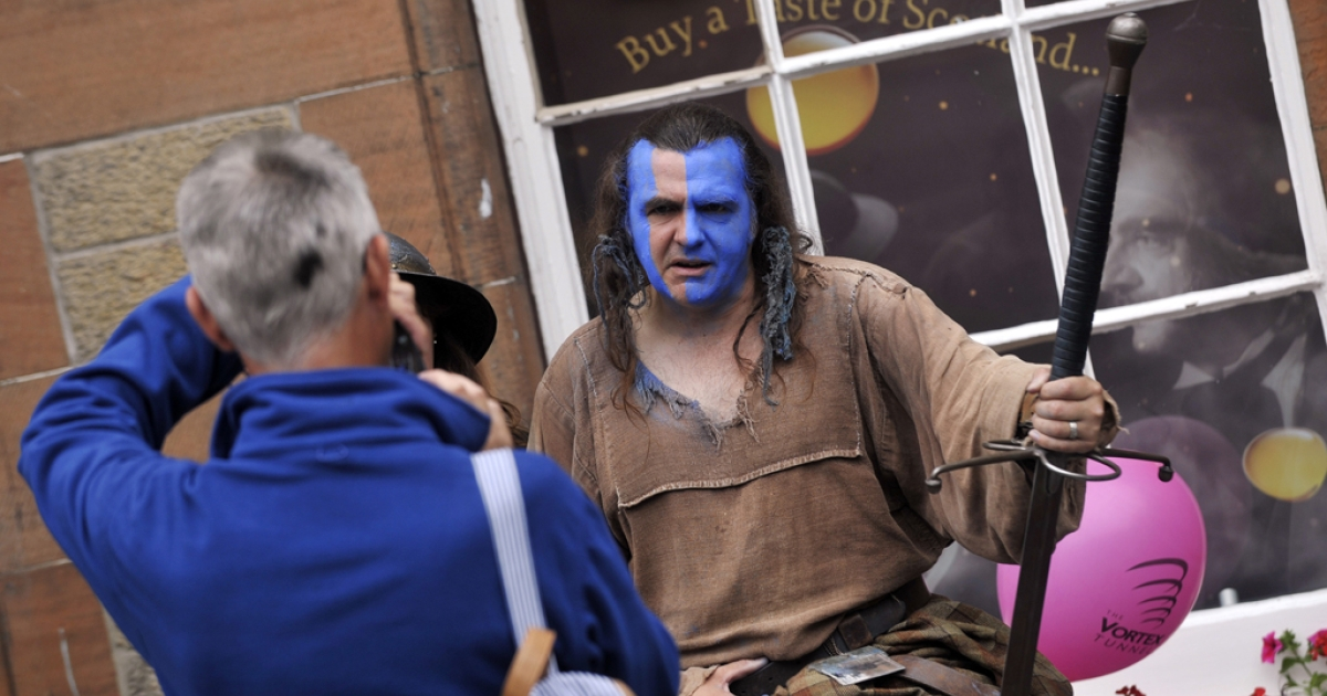 A member of the public takes a picture of a man dressed as the character William Wallace from Braveheart in Edinburgh on August 21, 2013 during the annual Festival Fringe.</p>