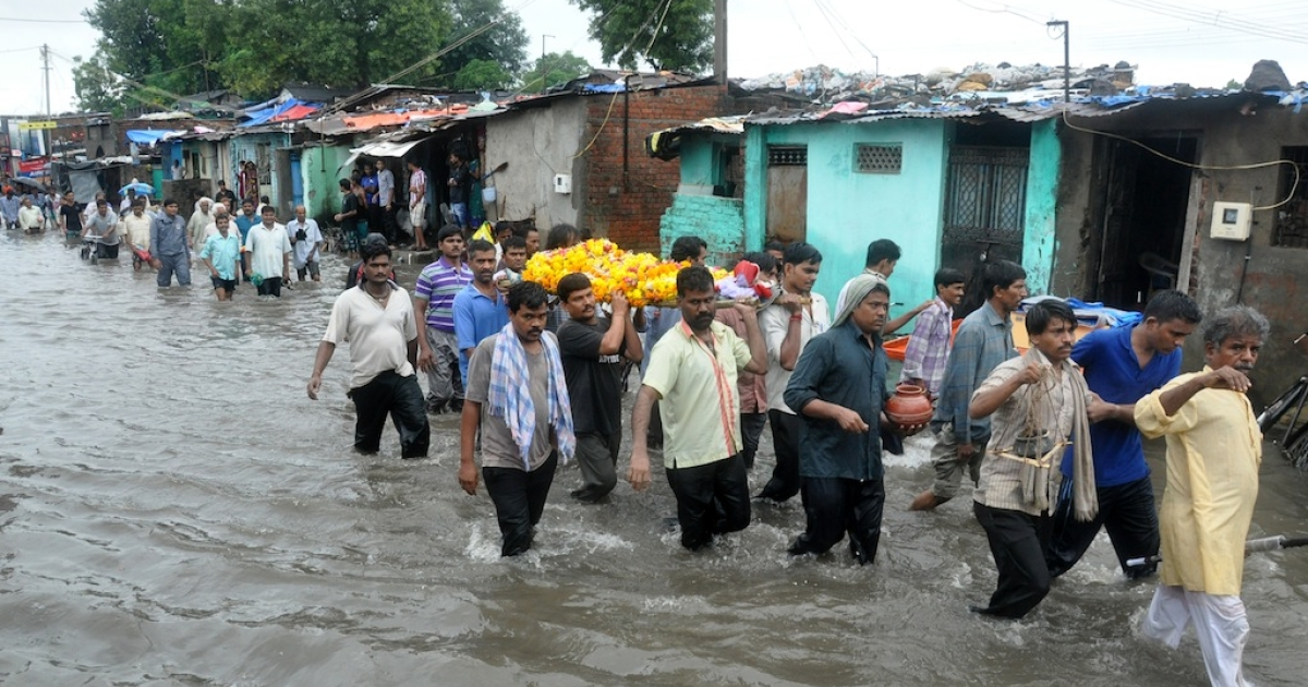 Indian mourners carry a body during a funeral procession as they wade through a flooded street in Vadodara, some 110 kms from Ahmedabad on September 24, 2013 .</p>