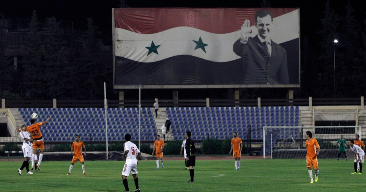 Syrian football players compete in front of a giant banner featuring Syrian President Bashar al-Assad during the Syrian Cup football match between Al-Wahda and the army's Al-Jaish teams on Sept. 10, 2013 in Damascus. Meanwhile, on the international diplomatic field, fumbles abound as the Russians intercept Kerry's desperation pass on the Syrian conflict.</p>