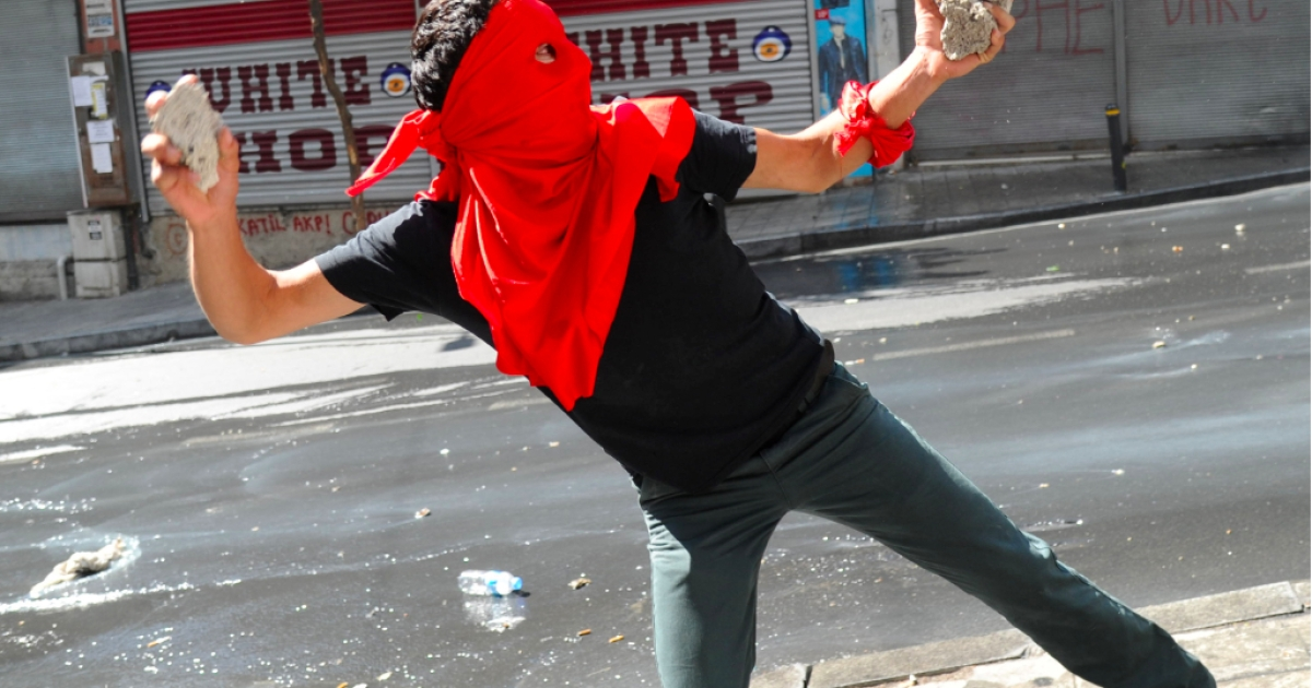 A Turkish leftist protester throws stones towards riot policemen during an anti-government demonstration in Istanbul on September 9, 2013.</p>