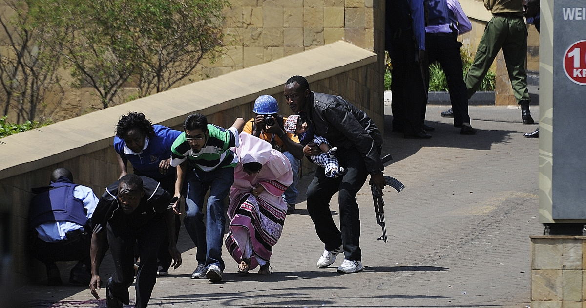 A policeman carry's a baby to safety after masked gunmen stormed an upmarket mall and sprayed gunfire on shoppers and staff, killing at least six on September 21, 2013 in Nairobi. The Gunmen have taken at least seven hostages, police and security guards told an AFP reporter at the scene.</p>