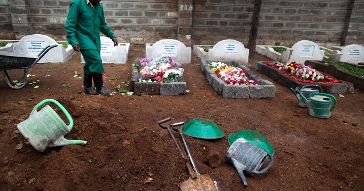 A cemetery worker walks next to fresh graves on September 25, 2013 after the funeral for Selima Merali, 41, and daughter Nuriana Merali, 15, who were killed in the attack by gunmen at the Westgate mall in Nairobi, Kenya. The country is observing three days of national mourning as security forces begin the task of clearing and securing the Westgate shopping mall following a four-day siege by militants.</p>