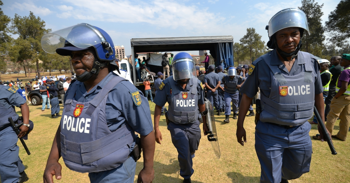 Riot policemen take their position during a demonstration of miners near South African government buildings in Pretoria, on September 12, 2013.</p>