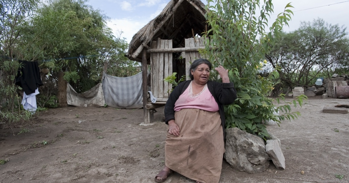 Maria Rufina Suarez sits outside her home in Vicente Guerrero, Mexico, listening to the benefits of registering with the government's