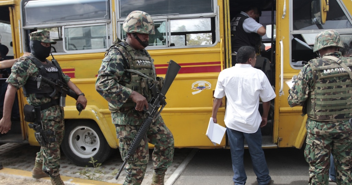 Forensic personnel work a crime scene in which a bus driver and his two assistants were killed by gunmen inside a bus in Acapulco's Cayaco neighborhood, in the state of Guerrero, Mexico, on March 11, 2013.</p>
