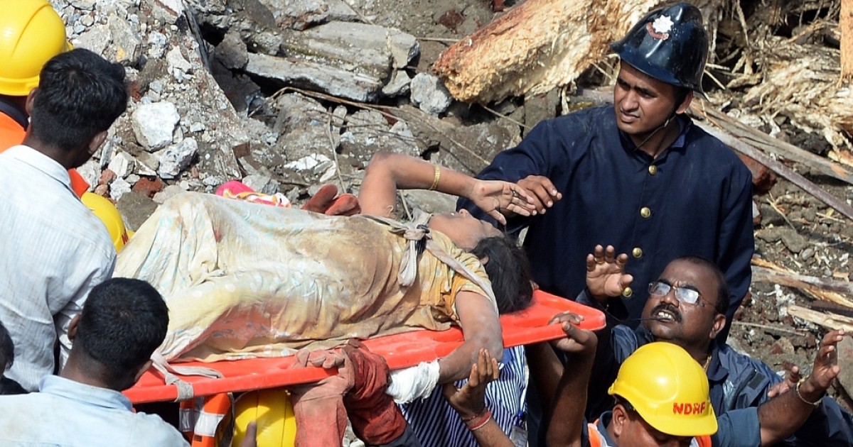 Firefighters bring out a female survivor from the rubble at the site of a building collapse in Mumbai on September 27, 2013. A five-storey residential block collapsed in Mumbai at daybreak killing at least three people and leaving up to 70 feared trapped inside, in the latest building disaster to hit India's financial capital.</p>