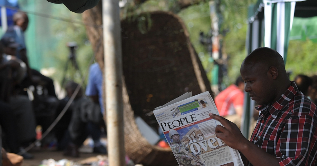 A man reads today's paper in Nairobi on September 25, 2013 after Kenyan forces took back control of  Westgate mall following a deadly four-day siege that left more than 60 people dead.</p>