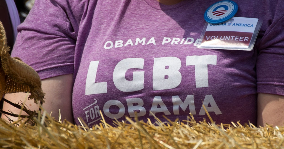 A President Barack Obama supporter with a lesbian, gay, bisexual, transgender slogan on her T-shirt listens to him speak during a campaign event in Maumee, Ohio, on July 5, 2012.</p>