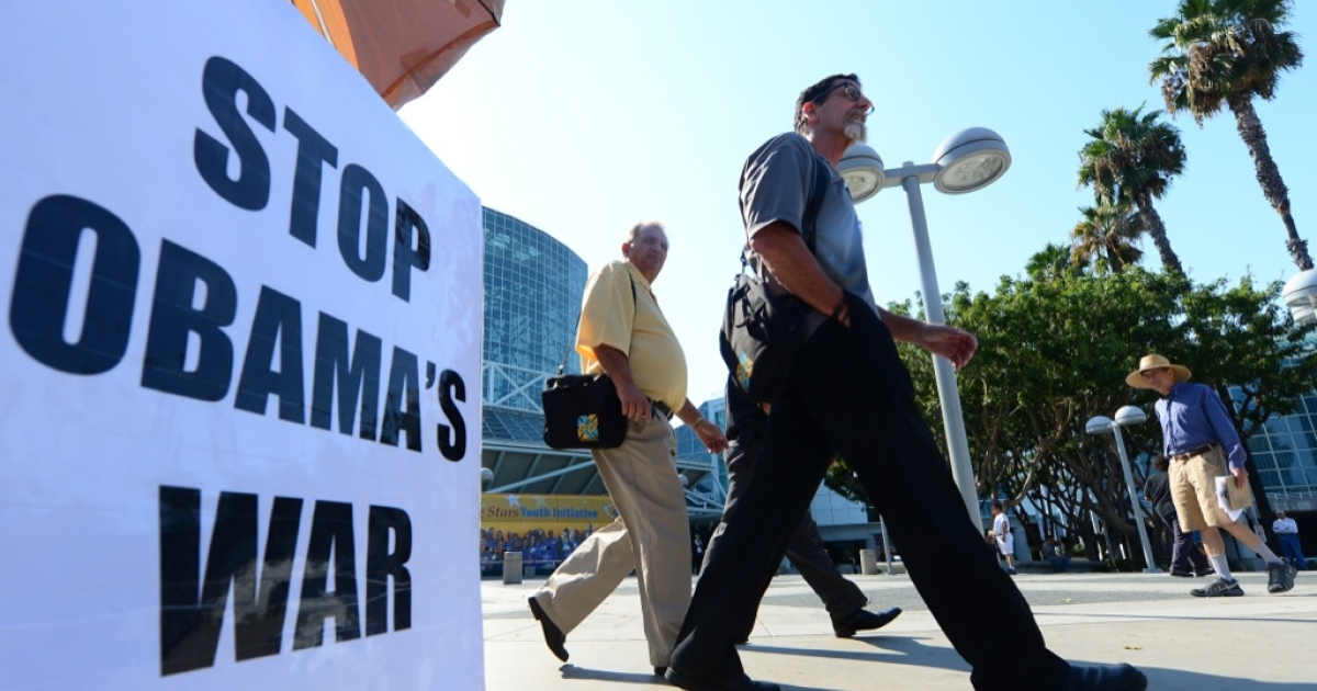Pedestrians walk past a placard that reads 'Stop Obama's War' outside the Los Angeles Convention Center on Sept. 9, 2013, as US President Barack Obama said a Russian plan to secure Syria's chemical weapons could be a 'significant breakthrough' but warned he had not taken US strikes off the table.</p>